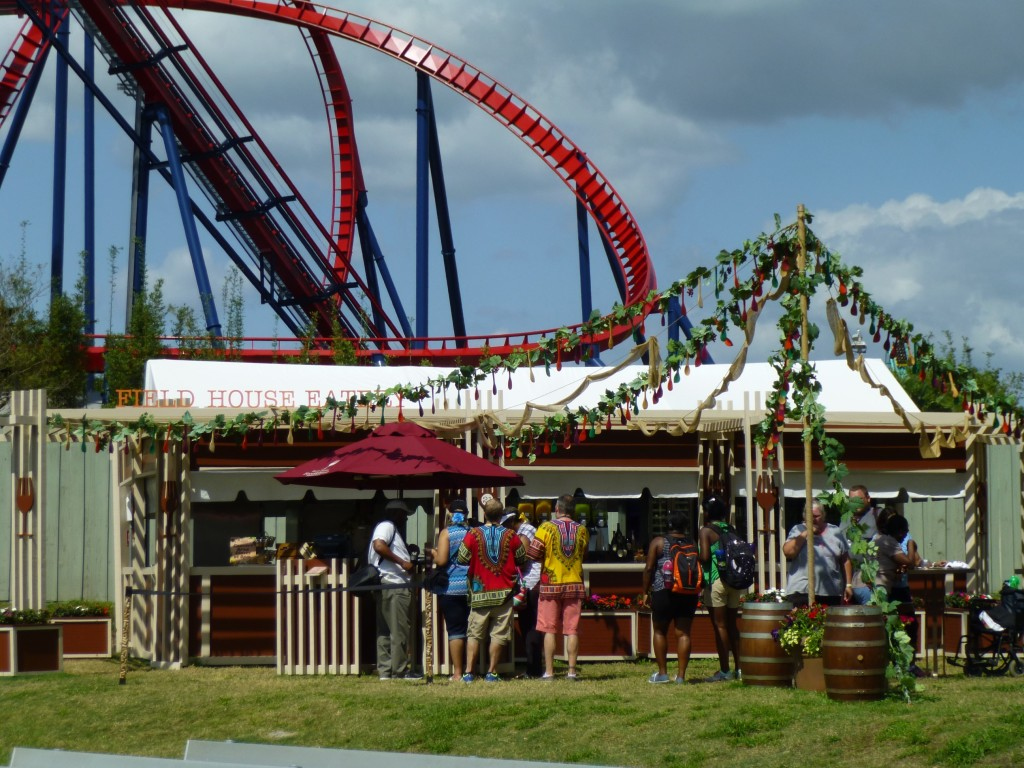 People lining up for food with the Shiekra coaster looming above
