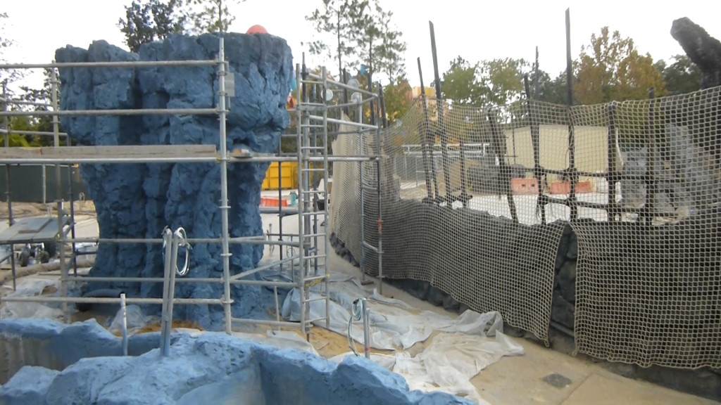 Rock formation on left, portion of outdoor ride path on right behind netting