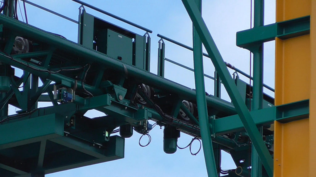 Close up of lift track meeting ride track. Motorized tires propel cars forward onto ride track
