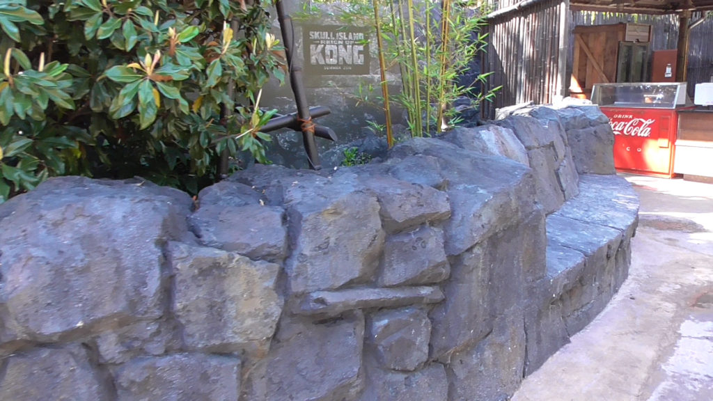 New rock wall facing walkway with built-in bench and hidden speaker playing new area music