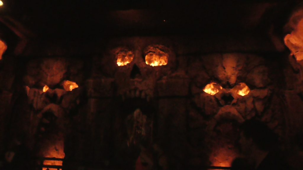 Animatronic woman in a room filled with skull and ape carvings filled with an impressively real looking fire musion effect