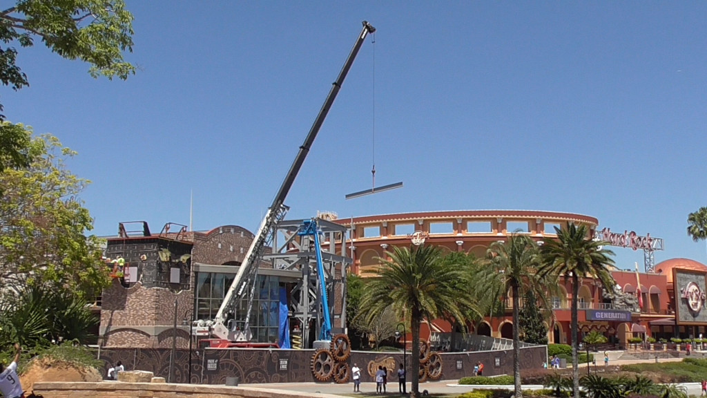 Crane lifting steel beam into place, as the facade grows