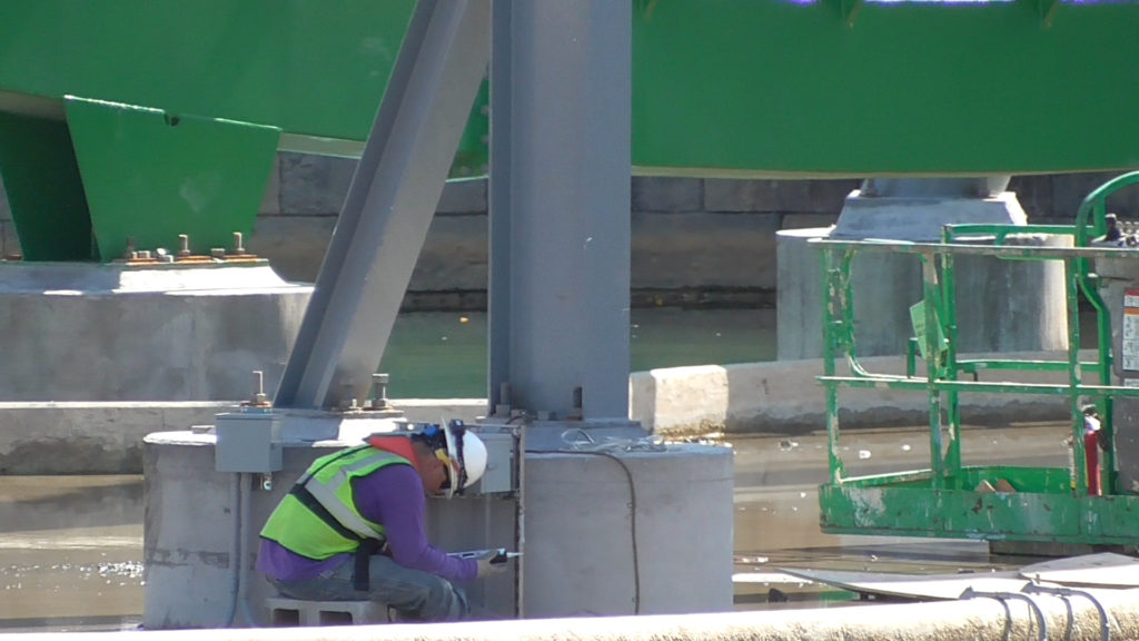 Workers installing electrical boxes at base of supports