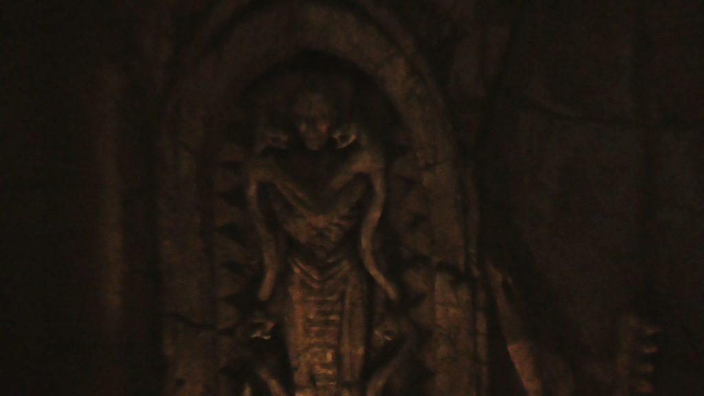 Inside the dark indoor queue, first room has two creepy statues and an arch to enter the next room that looks like a face