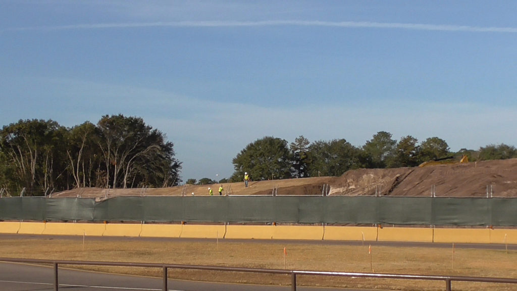 Wide view of new berm. Will probably be covered in grass and new plants will be added behind it soon to better block the area